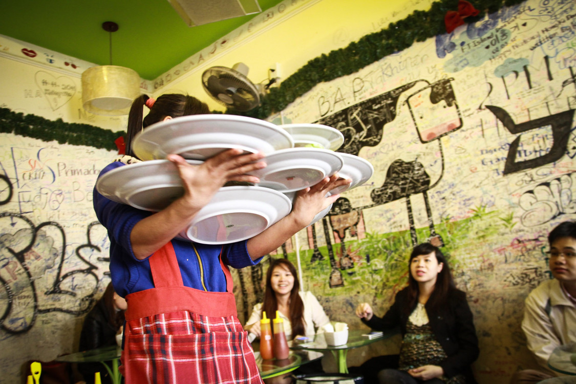 A waitress, who is a student on her part-time job at a local restaurant, manages to bring dishes to her customers.