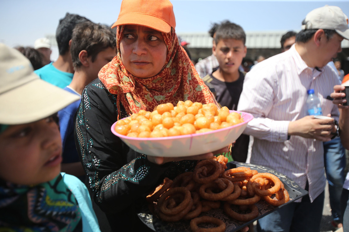 AL-AZRAQ, JORDAN - APRIL 30: A Syrian refugee woman offers some sweets to the guests at the souk in the Al-Azraq camp for Syrian refugees on April 30, 2015 in Al-Azraq, Jordan. To celebrate the first anniversary of the camp's opening, UNHCR, Care and other partners innaugurated a multi-purpose sports ground, a souk in the market in Village 3, launced the 1st Azraq soccer cup, an open air cinema and other recreational activities for children and adults. The camp is located in the desert 110 km to the east of Amman and not far from the Syrian border (Photo by Jordan Pix/Getty Images)