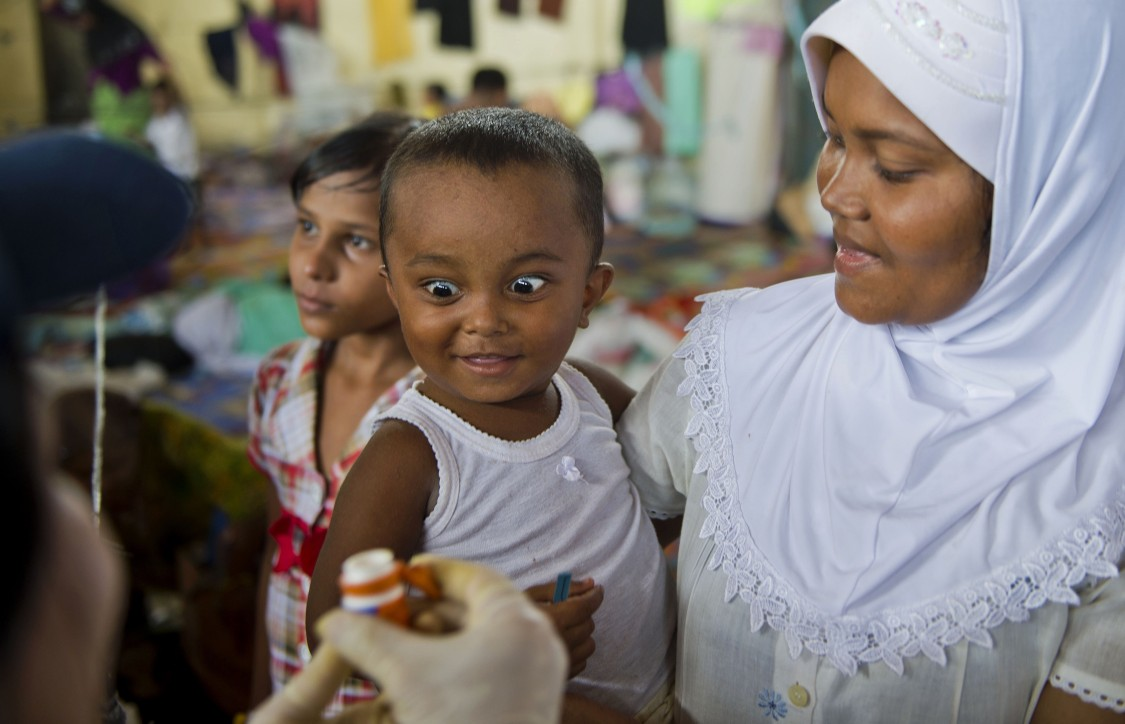 A Rohingya child (L) from Myanmar receives vitamin A from a medical team from the International Organization for Migration (IOM) while his mother (R) looks on, at the confinement area in the fishing port of Kuala Langsa in Aceh province on May 18, 2015 where hundreds of migrants from Myanmar and Bangladesh are taking temporary shelter after being rescued by Indonesian fishermen. Nearly 3,000 migrants have swum to shore or been rescued off Indonesia, Malaysia and Thailand over the past week, around half of whom have arrived in Indonesia's western province of Aceh. AFP PHOTO / ROMEO GACAD (Photo credit should read ROMEO GACAD/AFP/Getty Images)